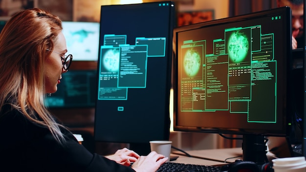 Girl hacker looking at super computer with multiple monitors while writing a malware.
