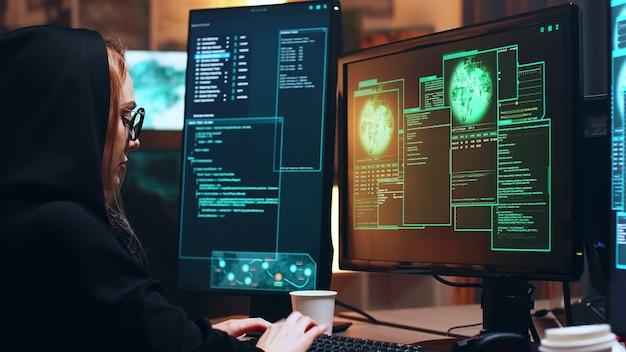 위험한 맬웨어를 사용하는 사이버 범죄를 위해 슈퍼 컴퓨터에 앉아 있는 소녀 해커.