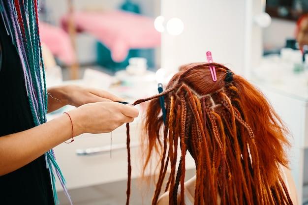 Девушка-парикмахер плетет женщине имбирные дреды и ножницами нарезает нитки, плетя косичку ...