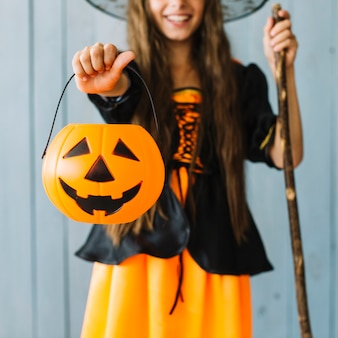 Girl in halloween costume holding basket in hand