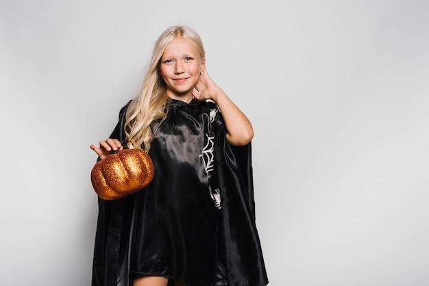 Girl in halloween costume holding pumpkin