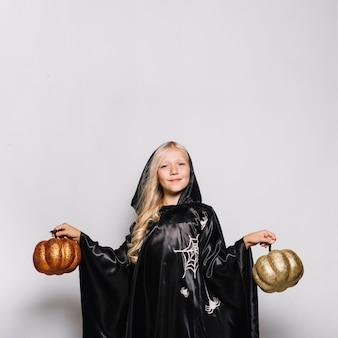 Girl in halloween costume holding pumpkins