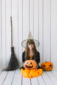 Girl in halloween costume sitting in studio with pumpkins and broom