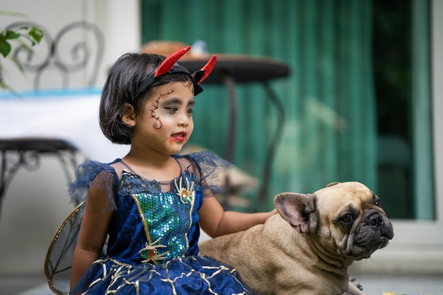 Girl in halloween costume sitting with french bulldog outdoor