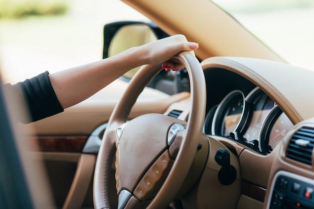 Mano della ragazza sul timone dell'auto