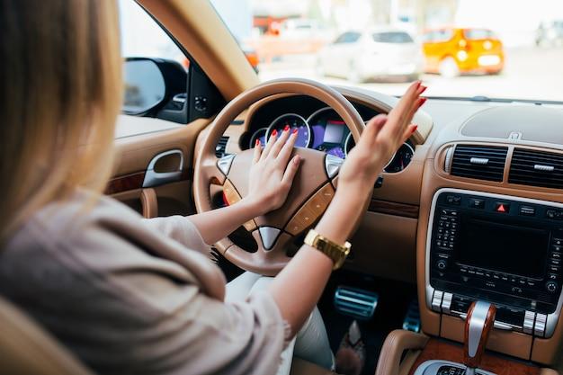 Segnale e auto con guida a mano della ragazza