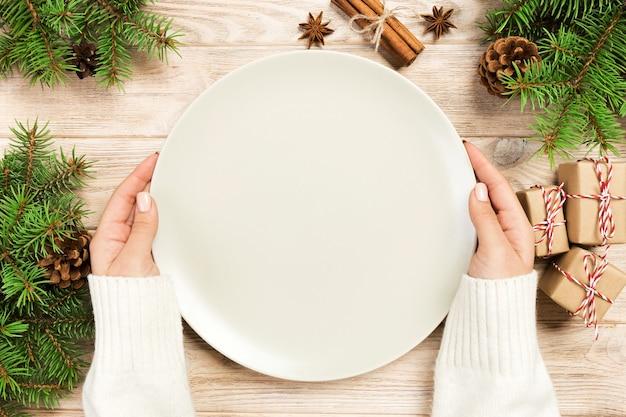 Удержание руки девушки пустая белая тарелка на деревянной предпосылке с украшением рождества. концепция нового года вид сверху.