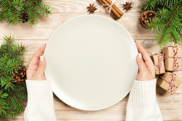 Girl hand hold empty white plate on wooden background with christmas decoration. new year concept top view.