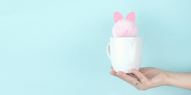 女の子の手はピンクのウサギのおもちゃが中にある朝のコーヒーカップを保持します。スペースをコピーします。青い背景。