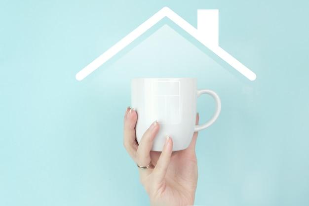Девушка рукой держать утреннюю кофейную чашку с знаком дома значок на синем фоне.