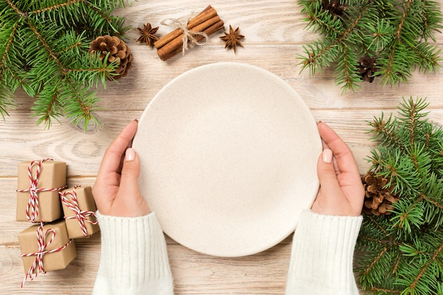 Girl hand hold top view. empty white plate on wooden background with christmas decoration. new year