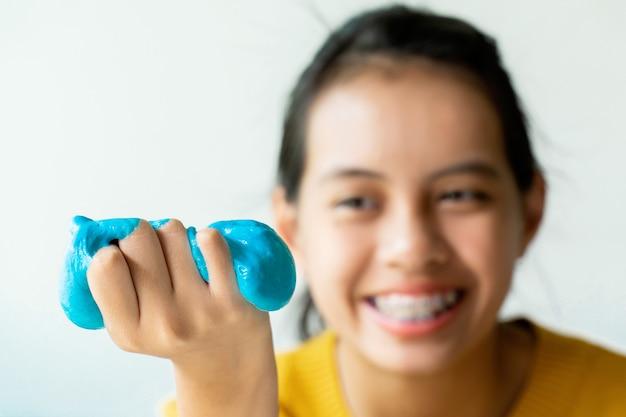 スライムと呼ばれる自家製のおもちゃを持っている女の子の手、