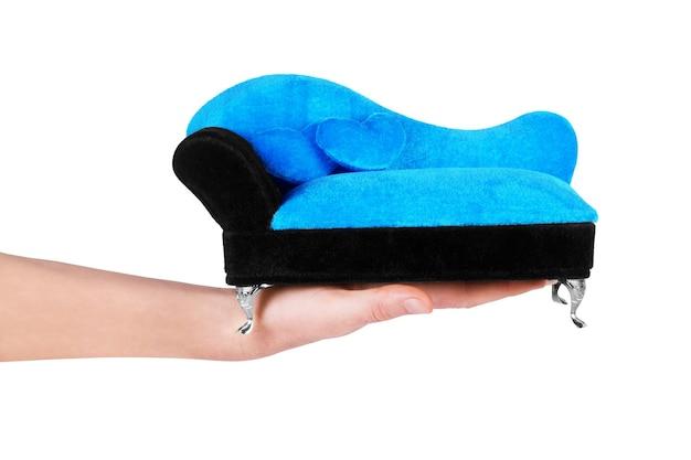 Girl hand holding mini sofa isolated on white background
