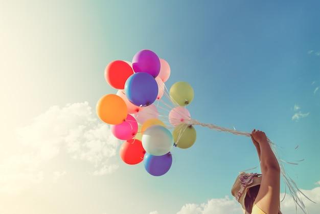 多色の風船を持つ女の子の手