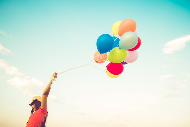 Girl hand holding multicolor balloons