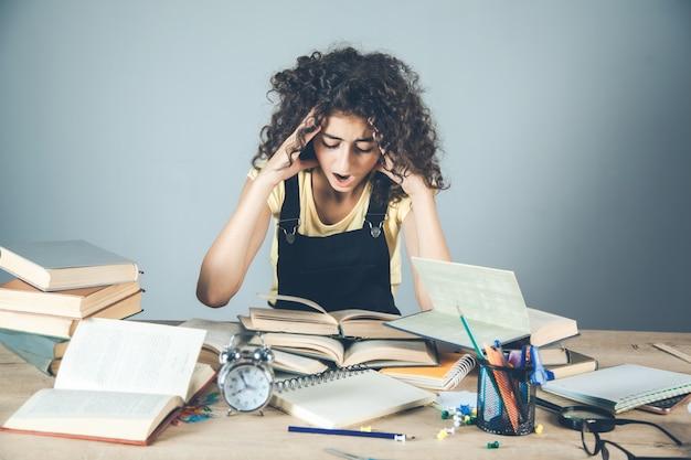 机の上の本と髪の少女の手