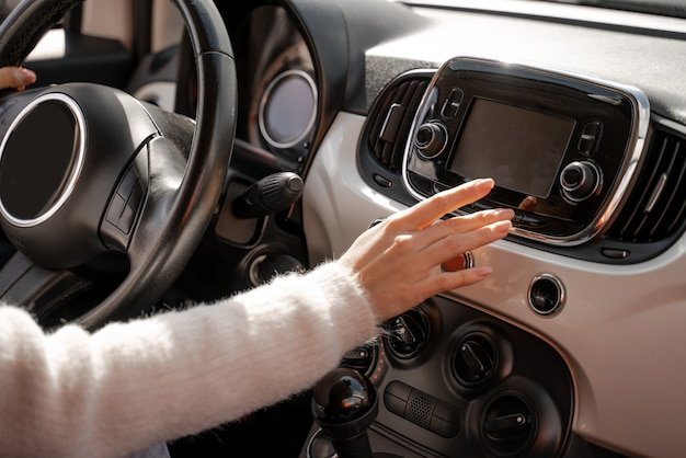 Girl hand pushing monitor screen in car. close up view. modern woman as driver in luxury automobile. concept of driving car