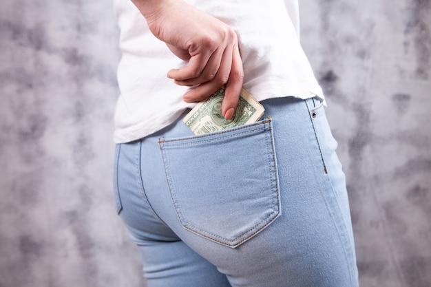 Девушка кладет деньги в карман джинсов