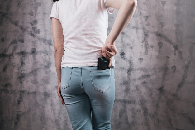 Девушка рука кладет бумажник в карман джинсов