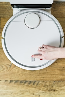 The girl hand switch on a robot vacuum cleaner.
