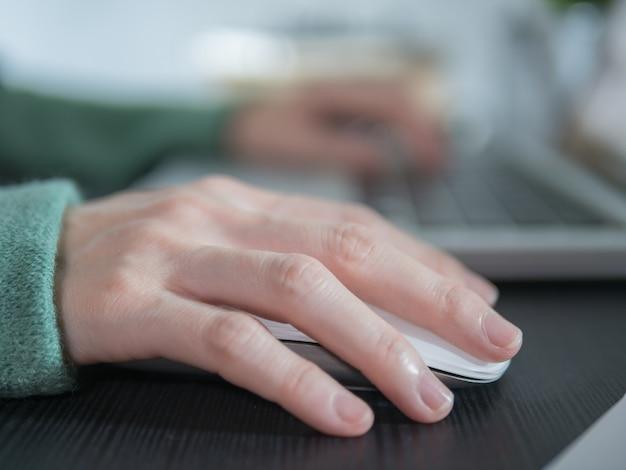 Рука девушки с помощью беспроводной мыши для ноутбука дома.