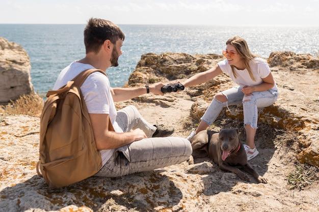 Girl handing a pair of binoculars to her boyfriend