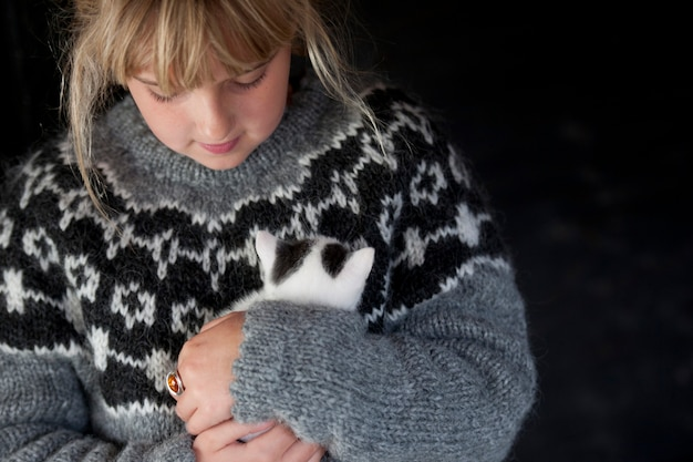 Girl in a handknit icelandic sweater holding a fluffy bank and white kitten in iceland