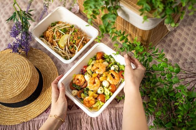 女の子の手はエビのサラダのプラスチック容器を持っています。オフィス、家庭、またはピクニックへの食品配達の概念。認識できない人