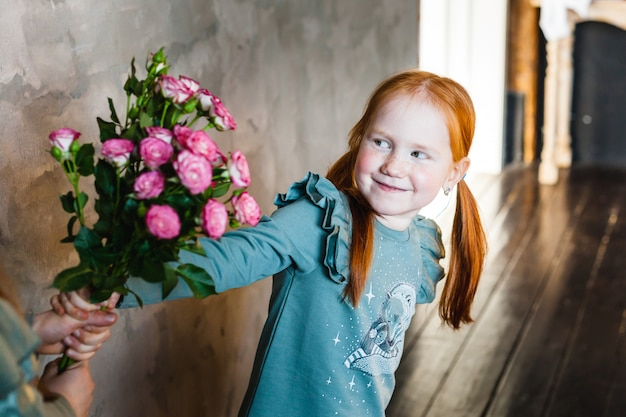 A girl hands a bouquet of roses to her mother or sister, joy, childhood, smile,
