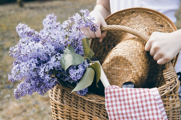 Girl hands carrying wicker basket with lilac flower bouquet