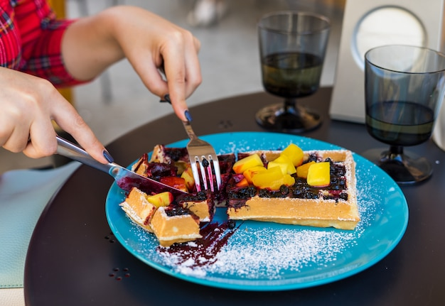 Girl hands cutting waffles with fruite.