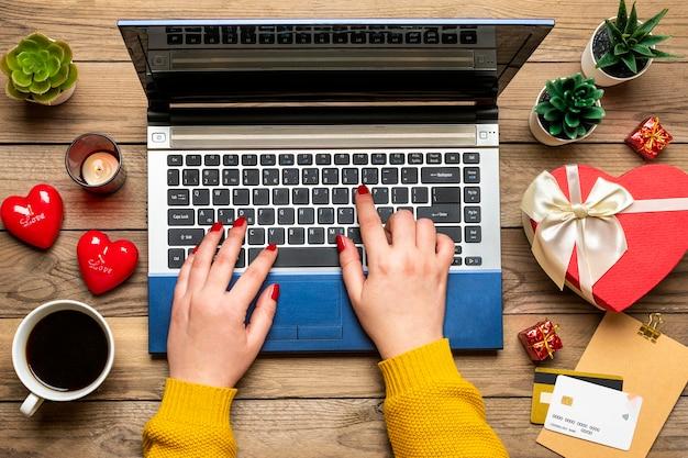 Руки девушки, дебетовая карта, выбирает подарки, делает покупки, планшет, чашка кофе, два сердца