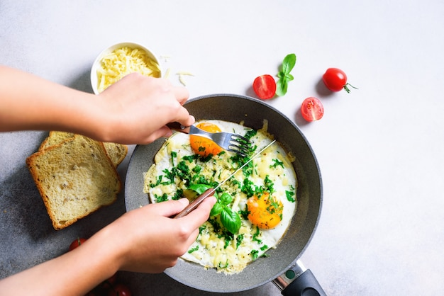 Girl hands above frying pan with three cooked eggs, herbs, cheese, tomatoes.