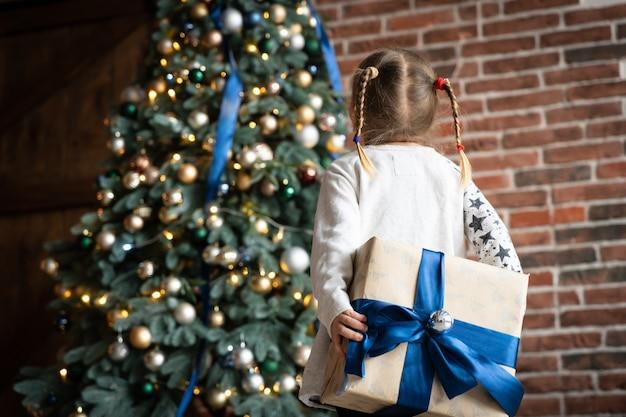 女の子の手は、クリスマスプレゼントや新年の装飾が施されたギフトボックスを保持します。喜び平和愛