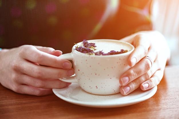 カプチーノのカップを保持している女の子の手