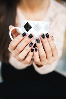 美しい黒のマニキュアとコーヒーのカップを保持している女の子の手。