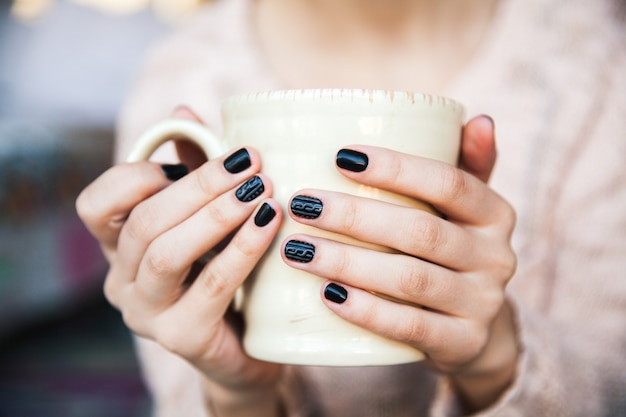Girl hands holding a cup of coffee with beautiful black manicure.