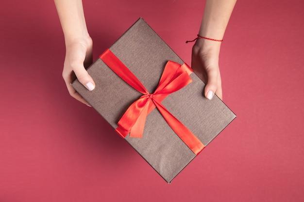 Девушка руки держит подарочную коробку на фоне бордо.