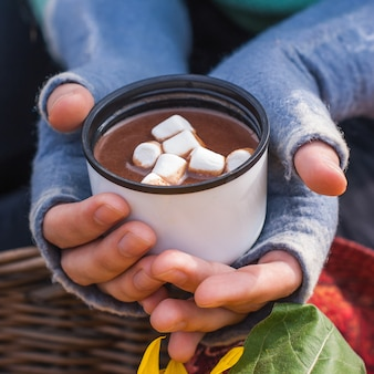 Girl hands holding a mug of hot chocolate or cocoa with marshmal