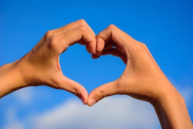 Девушка руки в форме сердца любви на синем небе с облаками.