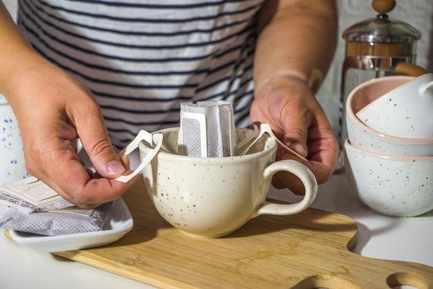 女の子がフレームに手を入れて、クローズアップして、バッグから淹れたてのコーヒーを瞬時に作ります。トレンディな種類のドリップコーヒー、カップ付きのテーブルの上の明るいキッチン、朝の太陽の光