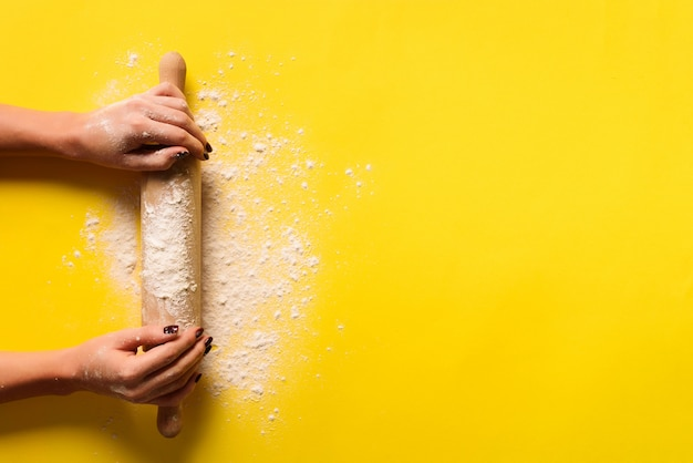 Girl hands keep rolling pin with flour on yellow background.