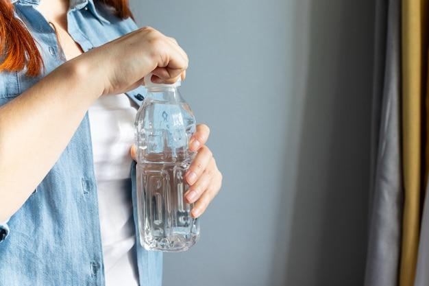 女の子の手が部屋に水のボトルを開きます。渇きのコンセプト
