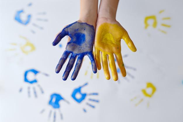 Руки девушки нарисованы гуашью, ребенок в мастерской