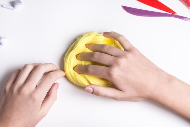 노란 점액을 가지고 노는 여자 손