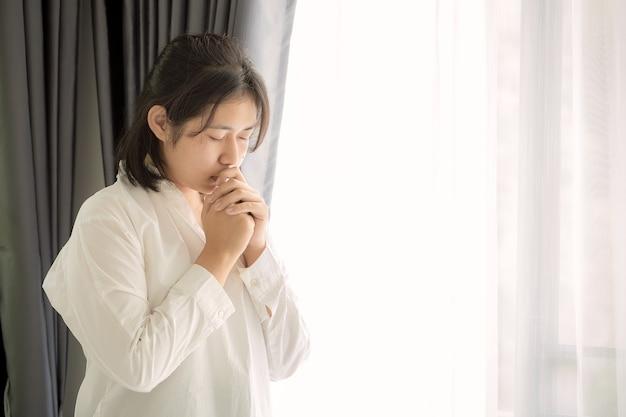 神に祈る少女の手。若い女性は、より良い生活を送りたいという神の祝福を祈っています。許しを乞い、善を信じます。神へのキリスト教の生命危機の祈り