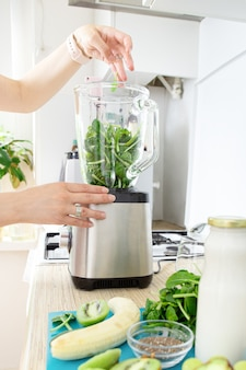 Руки девушки готовят зеленый смузи, кладут свежие листья шпината в блендер. концепция здорового питания. вегетарианство, веганская еда, фитнес-питание, детокс, сохранение молодости.