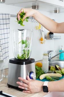 여자 손에 녹색 스무디를 준비하고 믹서기에 신선한 시금치 잎을 넣습니다. 건강한 먹는 개념. 채식주의, 비건 음식, 피트니스 음식, 해독, 청소년 보호. 프리미엄 사진