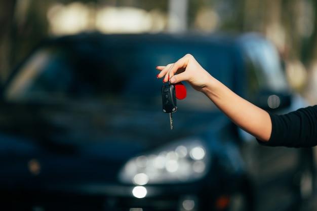 Mani della ragazza con la chiave della nuova automobile