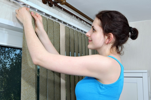 ブラインドをぶら下げている女の子は、垂直ブラインド生地のスラットがレールに引っ掛かります。
